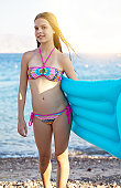Portrait of cheerful preteen girl with blue raft.