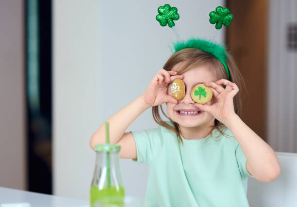 cheerful girl with cookie having a fun - st patricks day stock photos and pictures