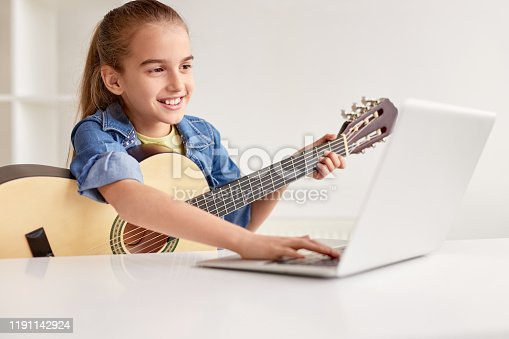 Happy little child in denim shirt learning to play guitar while watching lessons at laptop and smiling at home