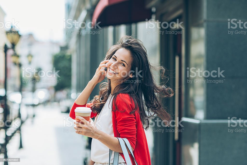 Cheerful girl with phone on the street looking back stock photo