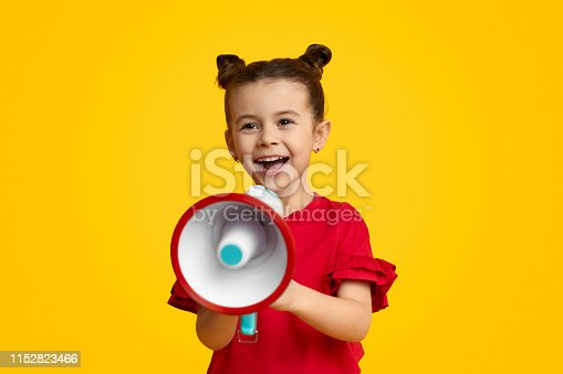 Excited kid leader speaking in megaphone and smiling while standing against yellow background. Young leader concept