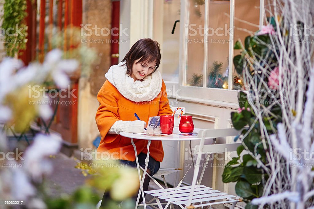 Cheerful girl writing Christmas cards in cafe stock photo