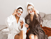 Cheerful multiracial girlfriends with face masks on wearing bathrobes drinking champagne, holding cucumber slices over eyes and smiling at camera, home interior