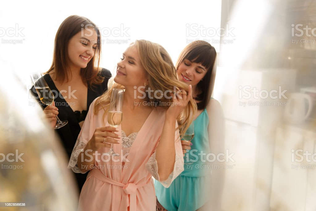 Cheerful girls drinking champagne at the bridal shower, at home stock photo