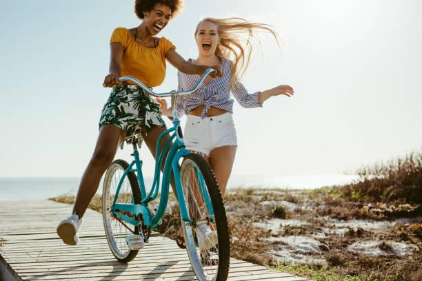 fröhliche mädchen mit spaß mit einem zyklus - freundin stock-fotos und bilder