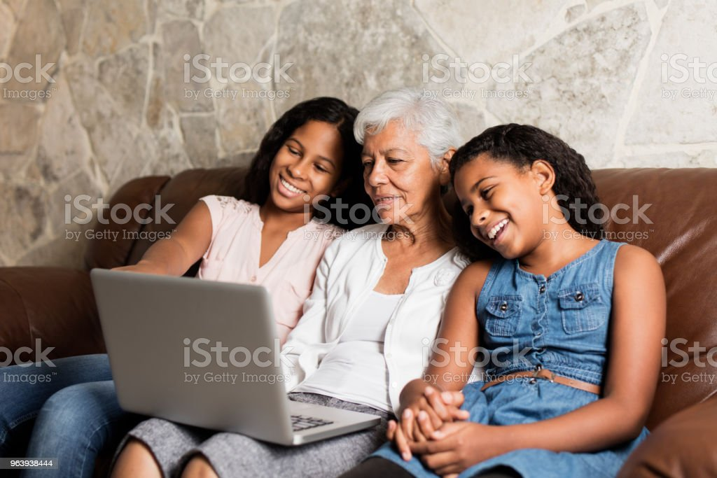 Cheerful girls looking at laptop with their grandmother - Royalty-free 12-13 Years Stock Photo