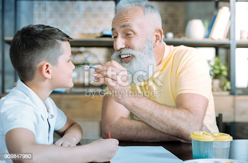 istock Cheerful granddad and child joking while painting at home 909847980