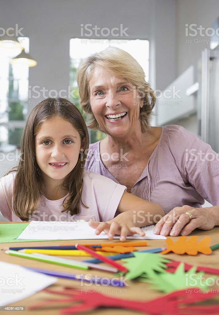 Cheerful granddaughter and grandmother drawing royalty-free stock photo