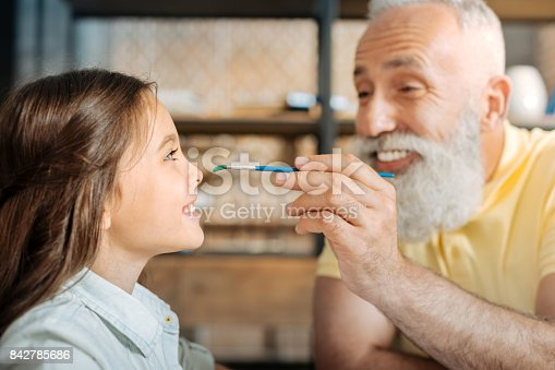 istock Cheerful grandfather painting nose of his granddaughter 842785686