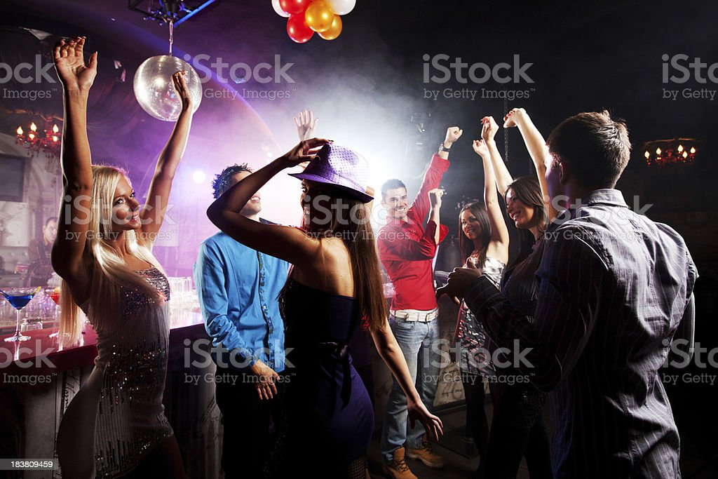 Cheerful group of a boys and girls enjoying at discotheque. royalty-free stock photo