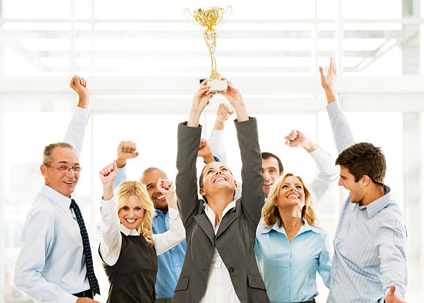 cheerful group of businesspeople winning the cup with hands up. - trophy award stock photos and pictures