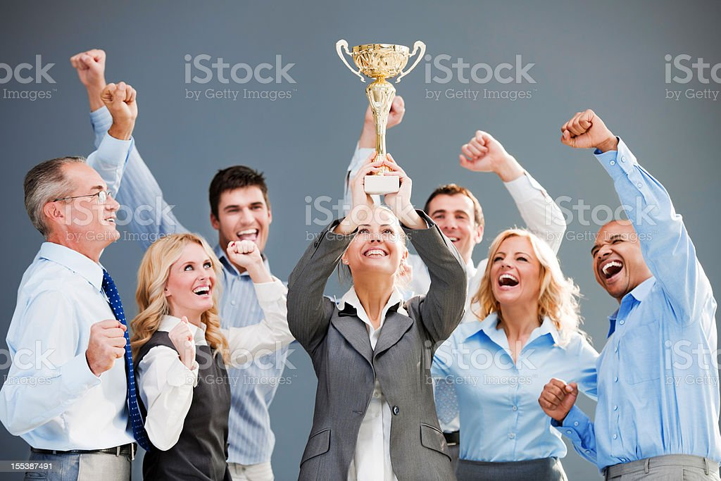 Cheerful group of businesspeople winning the cup with hands up. stock photo