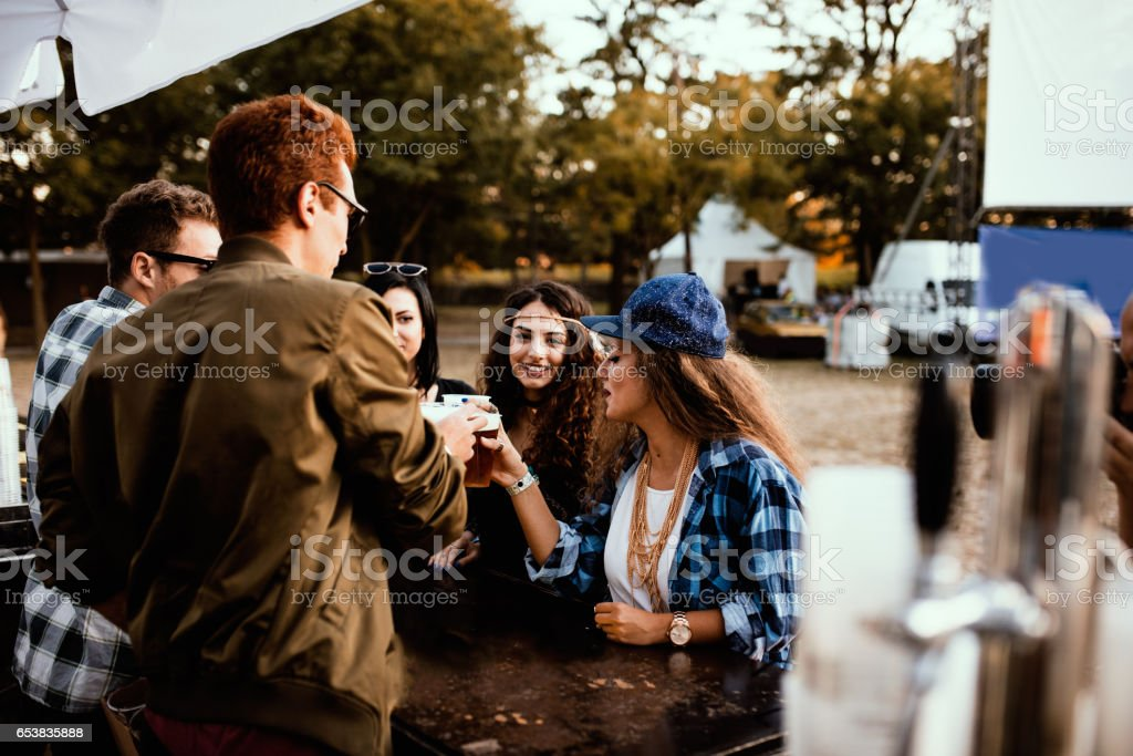 Cheerful group of friends drinking beer on the campsite at a music festival stock photo