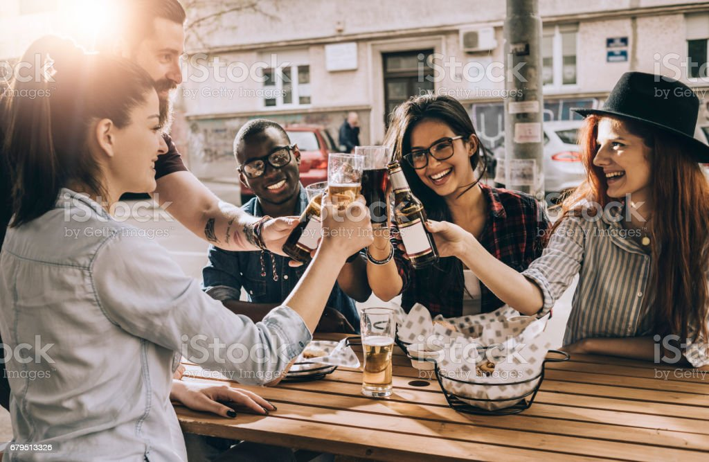 cheerful group of friends having fun and clinking their glasses - foto stock