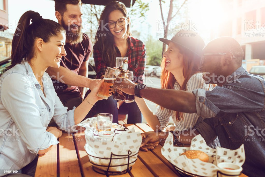 cheerful group of friends having fun and clinking their glasses royalty-free stock photo