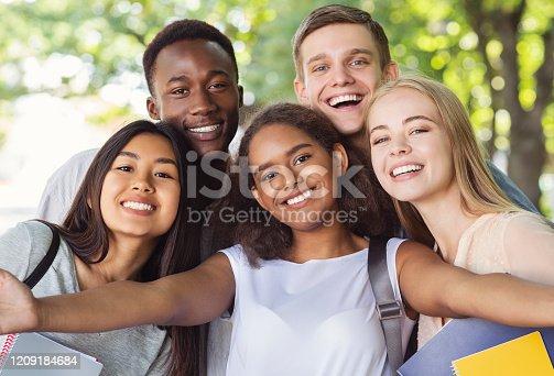 Cheerful international friends teenagers taking selfie while walking in summer park, happy memories concept