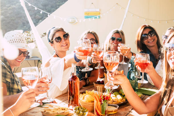 cheerful group of happy female people clinking and toasting together with friendship and happiness - young and adult women have fun eating - food and beverage celebration concept - поздний завтрак стоковые фото и изображения