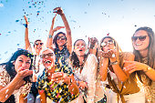 istock Cheerful group of happy people mixed ages generations women having fun all together during celebration party or carnival - view of fiends blowing. coloured confetti and laugh a lot in friendship 1200145880