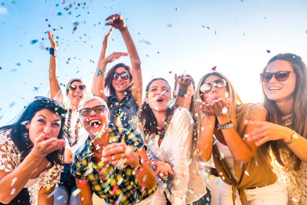 grupo alegre de personas felices mezclando edades generaciones mujeres divirtiéndose todas juntas durante la fiesta de celebración o carnaval - vista de demonios soplando. confeti de colores y reír mucho en la amistad - fiesta fotografías e imágenes de stock