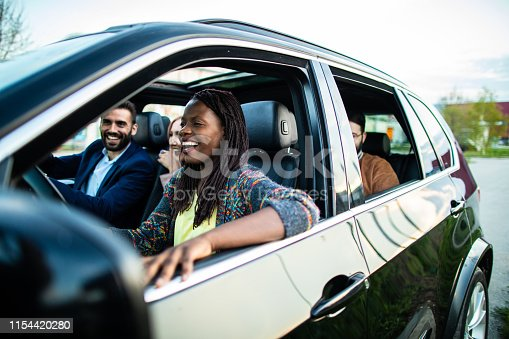 Multi-ethnic group of cheerful friends sitting in a car, riding and having fun on beautiful summer day