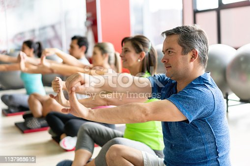 Cheerful group of people at a class in the gym stretching their arms - Lifestyles