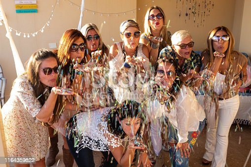 1016084100istockphoto Cheerful group of people blowing on the confetti to celebrate a party.  Nine beautiful women in friendship. Sunset on the terrace field 1164359822