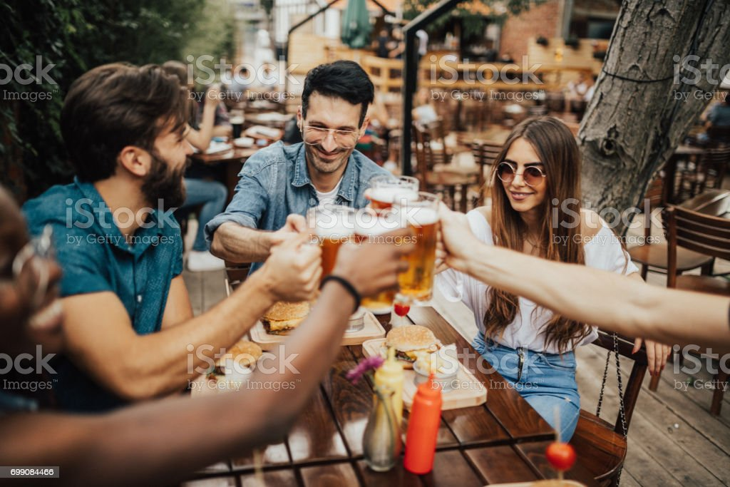 Cheerful group of people having fun in the pub stock photo