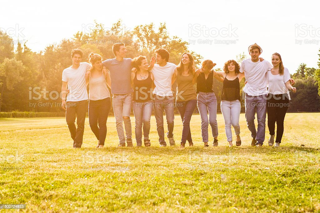 Cheerful group of teens walking in the park stock photo