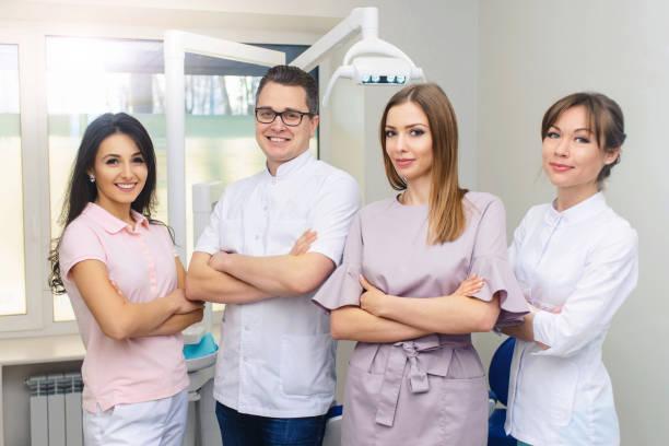 fröhliche gruppe von jungen zahnärzten und ihren assistenten stehen in der zahnarztpraxis und schauen auf kamera und freundlich lächelnd auf weißem hintergrund des medizinischen raumes. - sprechstundenhilfe stock-fotos und bilder