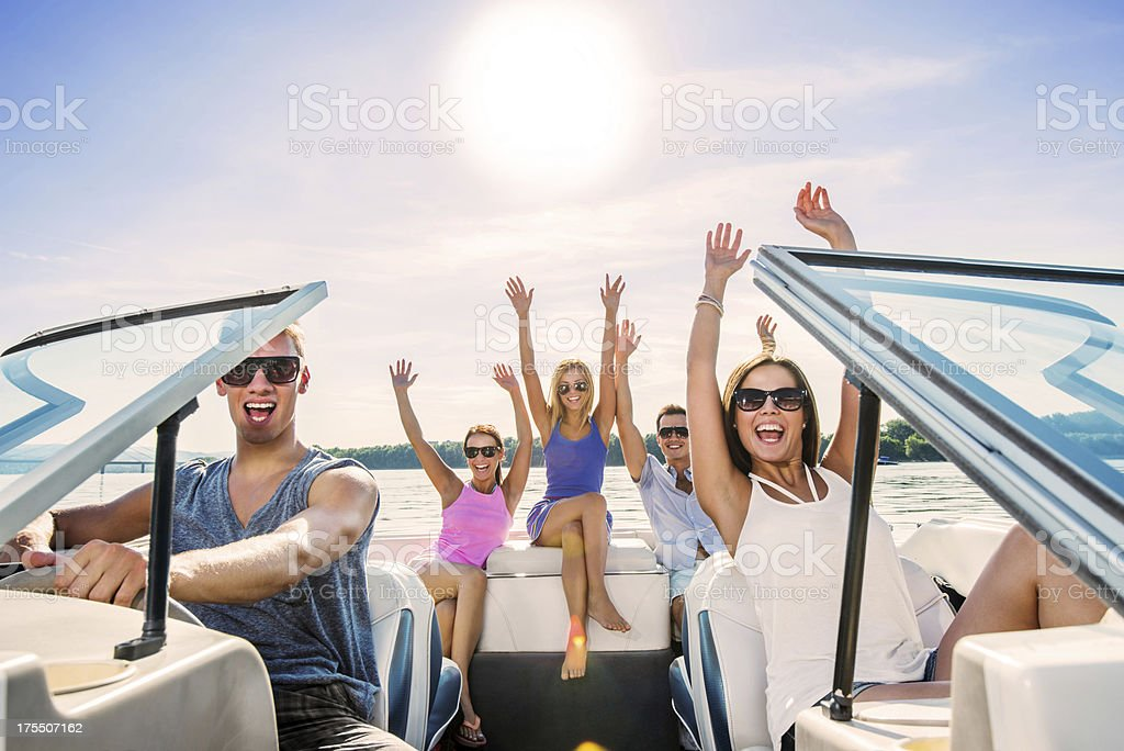 Cheerful group of young people enjoying in speedboat ride. royalty-free stock photo