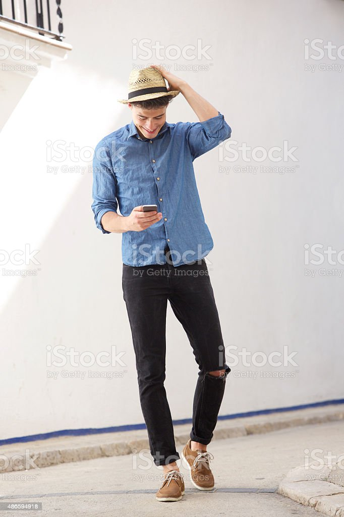 Cheerful guy walking and reading text message on cell phone stock photo