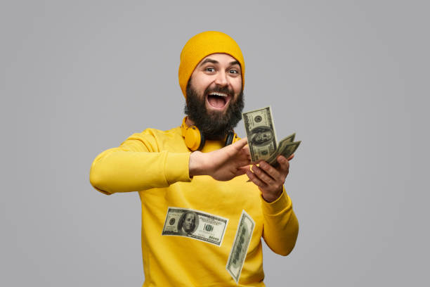 cheerful guy wasting money - throw money away stock pictures, royalty-free photos & images