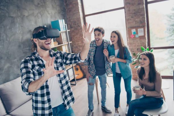 fröhlicher mann trug virtual-reality-brille, erste erfahrungen im umgang mit vr-kopfhörer, gestikulierend, berührende etwas mit waffen im büro während der kaffeepause - spiel des wissens stock-fotos und bilder