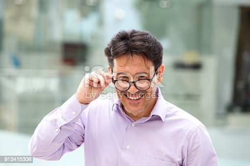 825083248istockphoto cheerful guy with glasses standing outdoors 913415306
