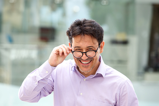 825083248 istock photo cheerful guy with glasses standing outdoors 913415306