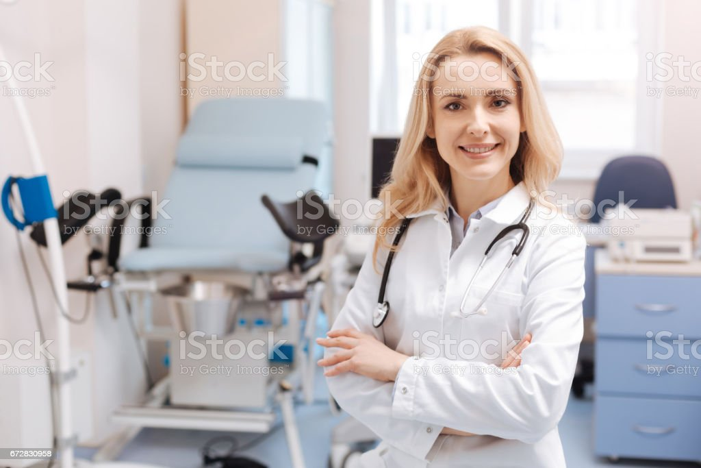 Cheerful gynecologist waiting for the next patient in the cabinet stock photo
