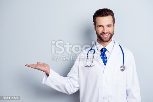 istock Cheerful handsome bearded smiling guy is holding the copy space. Doc is wearing white uniform and a tie, stands on a light white background 935414890