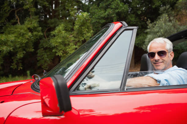 fröhlich gut aussehender mann genießen seine rote cabrio - 1m coupe stock-fotos und bilder