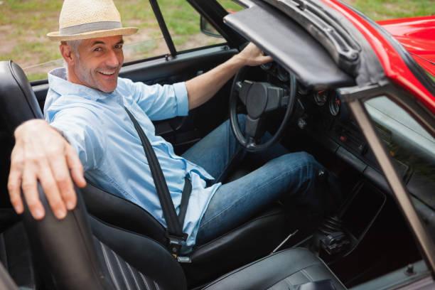 fröhlich gut aussehender mann posieren in rote cabrio - 1m coupe stock-fotos und bilder