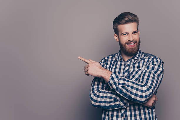 cheerful handsome  stylish man  pointing to the side - hipster persona foto e immagini stock