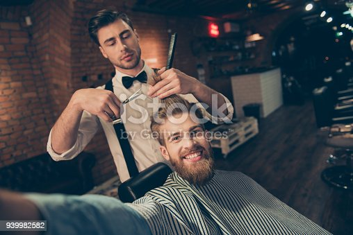 986804130istockphoto Cheerful handsome stylish red bearded guy with beaming smile is taking selfie at barber shop, stylish is making him a brand new haircut 939982582