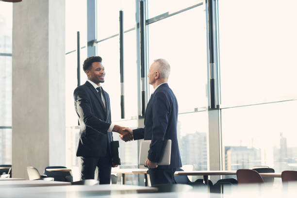 Cheerful handsome young African-American businessman in suit making handshake while greeting crisis manager into company stock photo