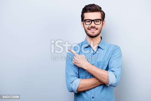 istock Cheerful handsome young man i glasses is showing direction and pointing with his finger 940470596