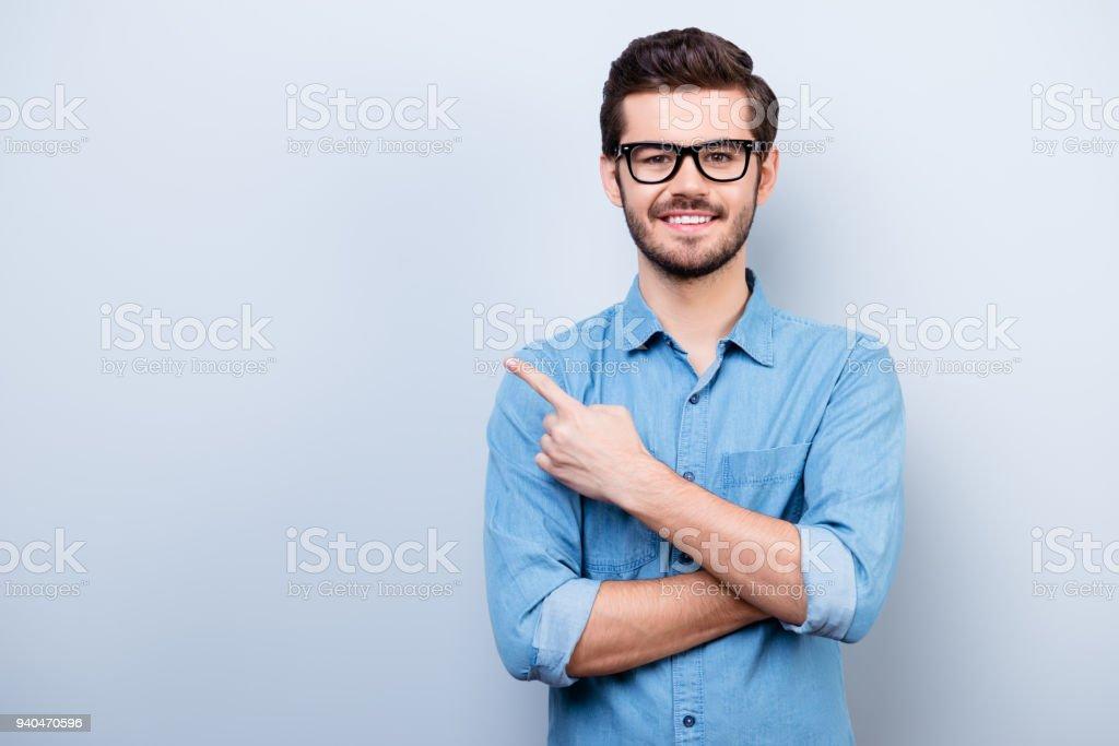 Fröhliche hübscher junger Mann ich Brille zeigt Richtung und zeigt mit dem Finger – Foto