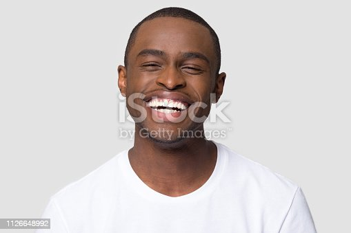 istock Cheerful happy african millennial man laughing isolated on studio background 1126648992