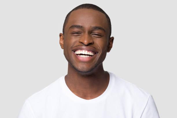 vrolijke gelukkig afrikaanse duizendjarige man lachen geïsoleerd op studio achtergrond - tanden bleken stockfoto's en -beelden