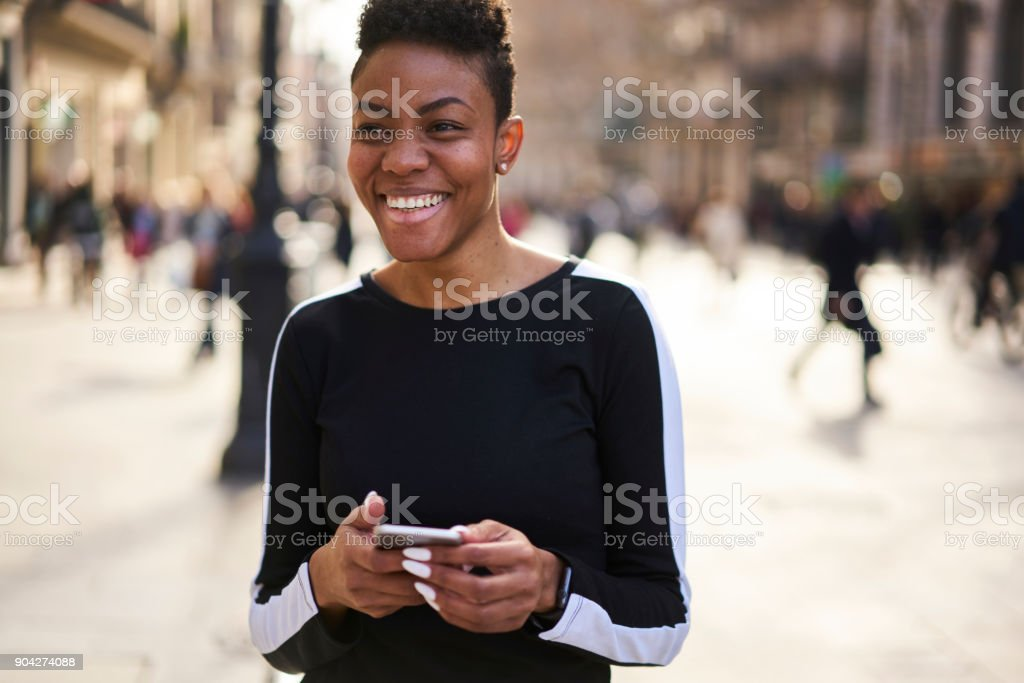 Cheerful happy afro american female communicating via smartphone chatting in social media outdoors, smiling black hipster girl having city tour strolling using online map application on smartphone stock photo