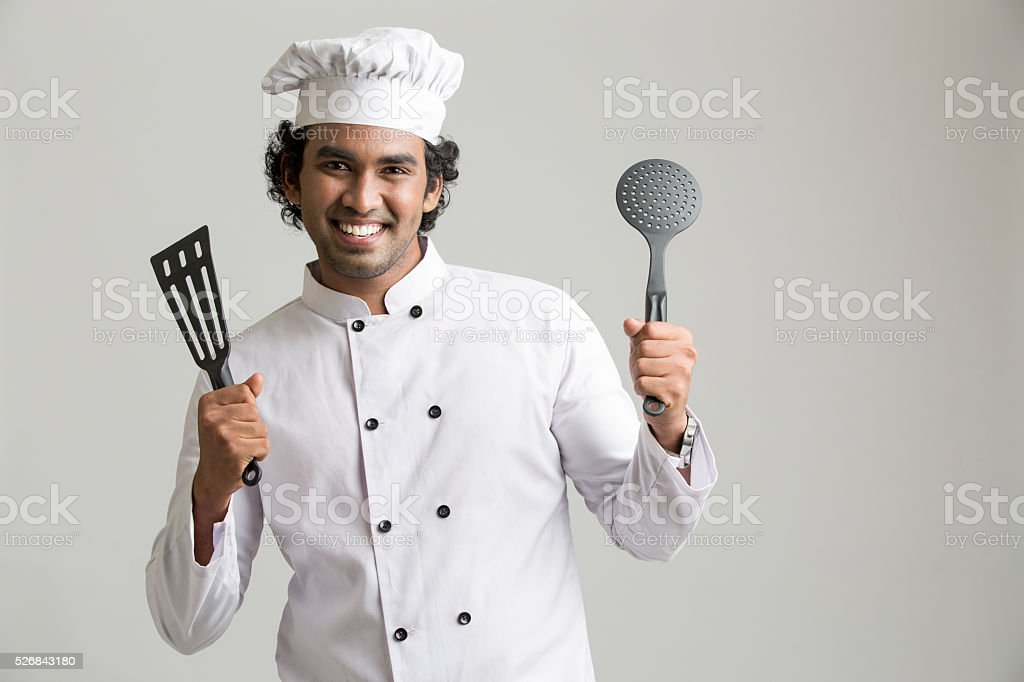 Cheerful happy chef holding kitchen stock photo