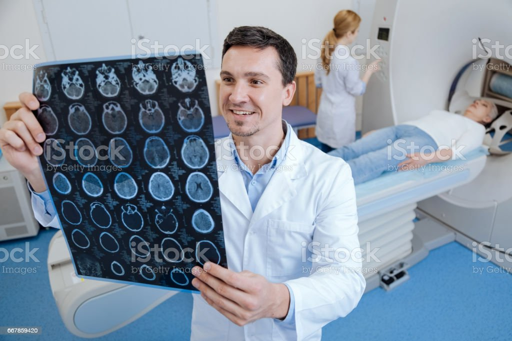 Cheerful happy doctor looking at MRI scan stock photo