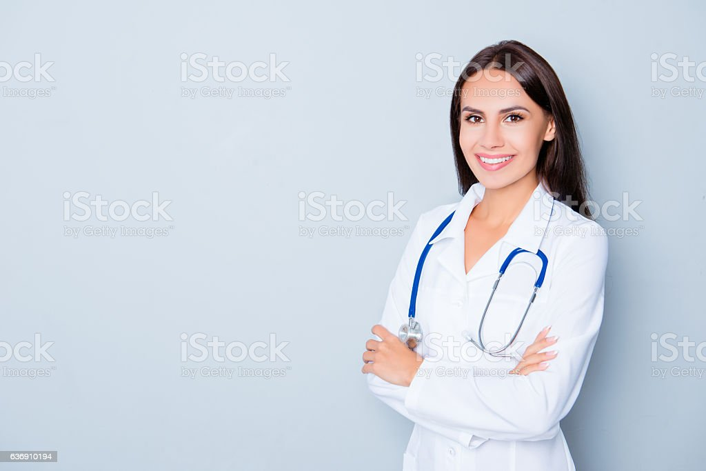 Cheerful happy doctor  with crossed hands on blue background stock photo